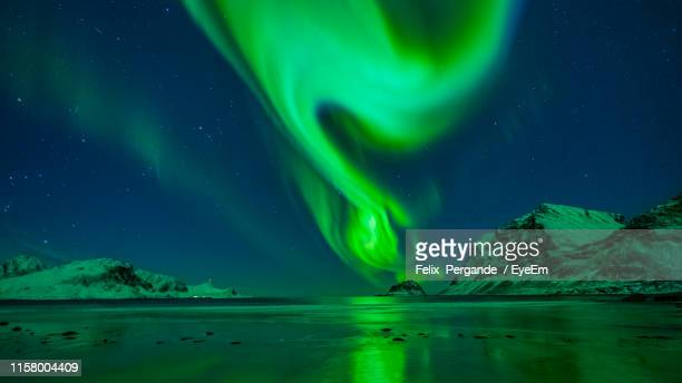 aurora borealis over sea against sky at night - フィンランド ストックフォトと画像