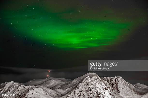 Aurora Borealis over snow covered fjord in Honningsvåg, Finnmark county, Norway