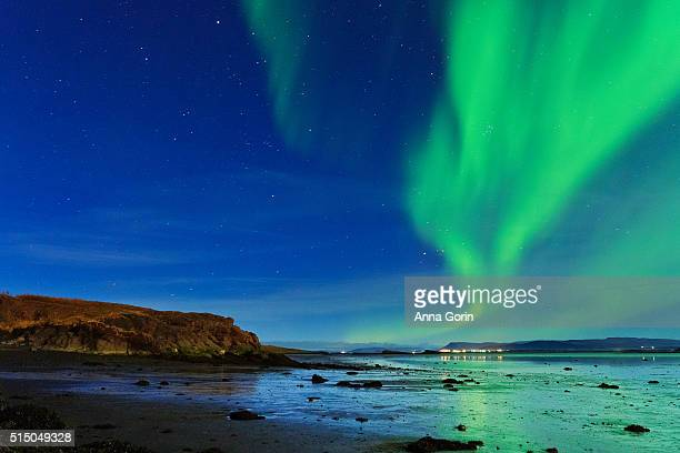 Aurora Borealis reflected at low tide on beach in Borgarnes, Iceland
