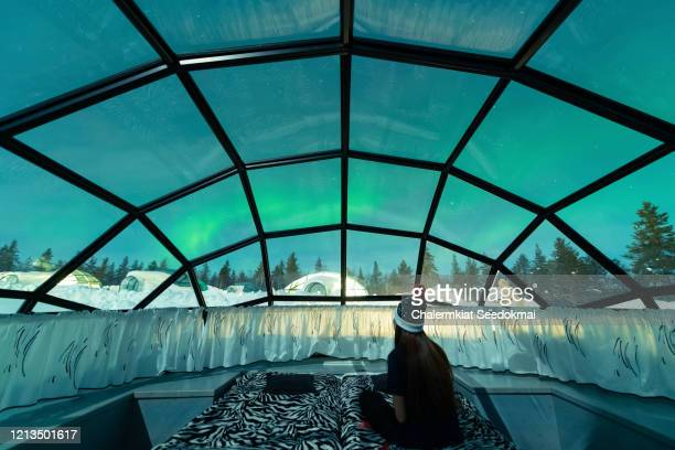 aurora borealis shining in the night sky seen from glass igloos - finland stock pictures, royalty-free photos & images
