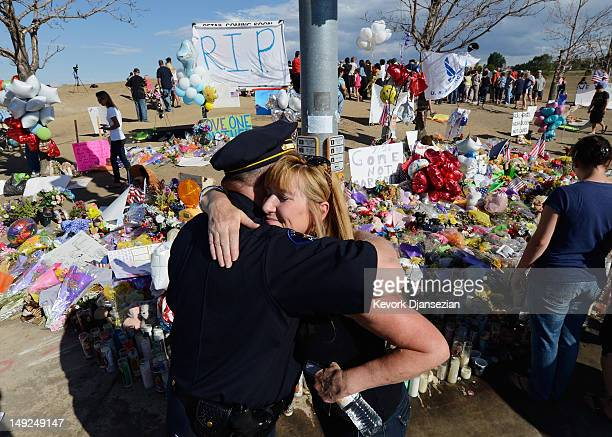 Aurora Colorado Police division chief Ken Murphy gets hug as he and Aurora police top brass along with firefighters visit the makeshift memorial...