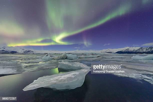 aurora displays over iceberg floating in lagoon - 氷河湖 ストックフォトと画像