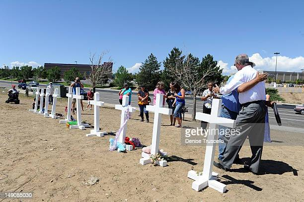 Aurora Mayor Steve Hogan stands in prayer with Greg Zanis from Aurora Ill who built and placed 12 white crosses in memoriam of the victims of...