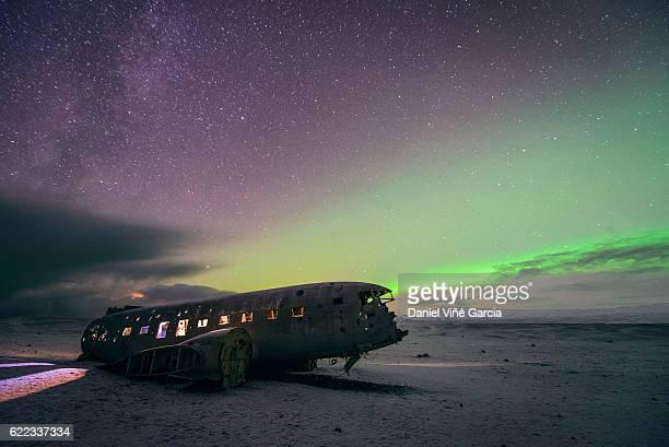Aurora milky way galaxy stars over plane crash beach Iceland