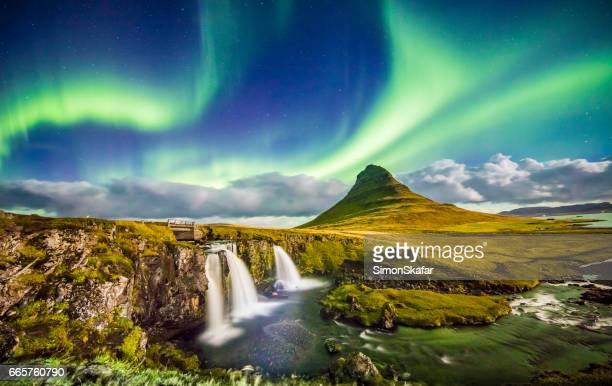 aurora over kirkjufell and waterfall at night - paesaggio spettacolare foto e immagini stock