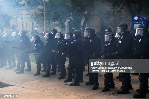 Aurora police officers charge towards Elijah McClain protesters at the Aurora Police department's headquarters at the Aurora Municipal Center June 27...