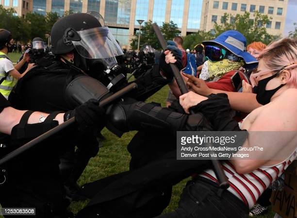 Aurora police officers clash with a protesters with batons during the Elijah McClain protest at the Aurora Municipal Center June 27 2020 Elijah...