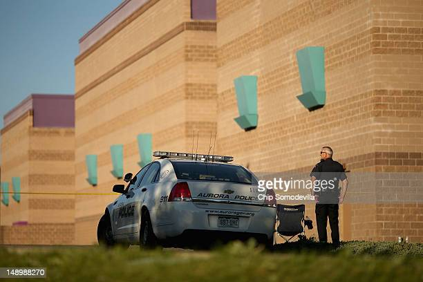 Aurora Police officers continue to maintain a secure perimeter around the Century 16 movie theater a day after a gunman killed 12 people and injured...