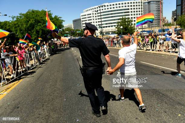 Aurora police Sgt Chris Amsler left holds the hand of his husband Manuel right as the two surrounded by supporters from the department take part in...