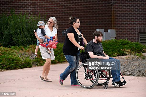 Aurora shooting victim Caleb Medley in wheelchair and his wife Katie middle with their baby boy Hugo arrive at the Arapahoe County Justice Center in...