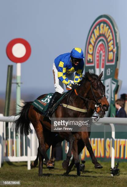 Auroras Encore ridden by Ryan Mania crosses the line to win the John Smiths Grand National at Aintree Racecourse on April 6, 2013 in Liverpool,...