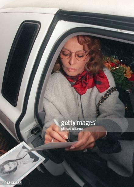 Aus einer großen Limousine heraus gibt die italienische Schauspielerin Sophia Loren nach ihrer Ankunft am auf dem Flughafen Hamburg Autogramme auf...