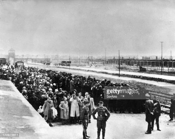 Auschwitz, poland, victims of the auschwitz concentration camp stand on the platform in birkenau station, awaiting selection for either the gas...