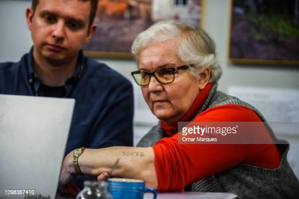 Auschwitz-Birkenau survivor Lidia Maksymowicz shows her prisoner tattoo number to an international audience during a Zoom platform meeting at the...