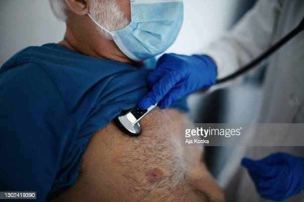 auscultating procedure on a senior patient. - mid section stock pictures, royalty-free photos & images