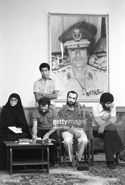 Ausländische Journalisten sitzen unter dem Bildnis von Revolutionsführer Oberst Muammar Abu Minyar alGaddafi während eines Pressegesprächs im...