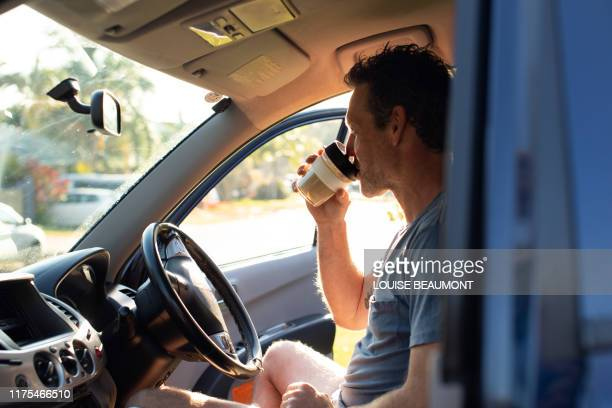 aussie bloke enjoys his morning coffee from an eco travel mug - morning photos et images de collection