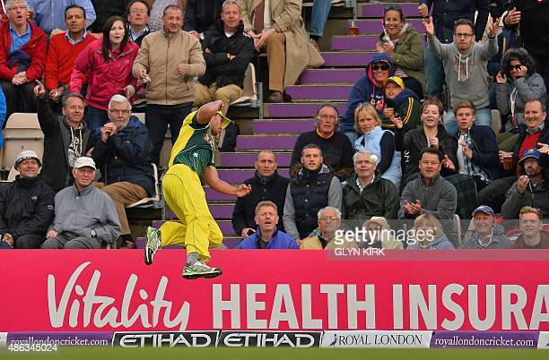 Austalia's Nathan CoulterNile jumps as he attempts to catch a shot from England's Alex Hales as the ball goes over the boundary for six runs during...