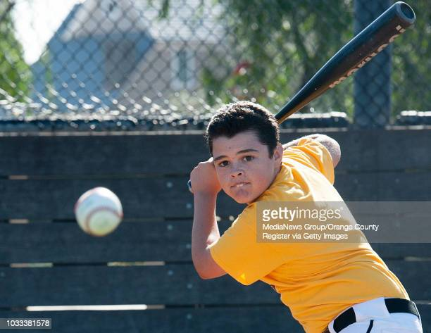 Austin Acevedo keeps his eye on the ball during batting practice with his dad as the Newport Beach Little League resumed their schedule after a 4day...
