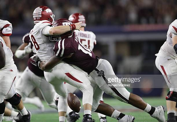 Austin Allen of the Arkansas Razorbacks fumbles the ball on the hit by Daeshon Hall of the Texas AM Aggies in the fourth quarter at ATT Stadium on...