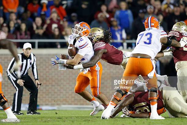 Austin Appleby of the Florida Gators fumbles the ball after being hit by Josh Sweat of the Florida State Seminoles in the first quarter of the game...