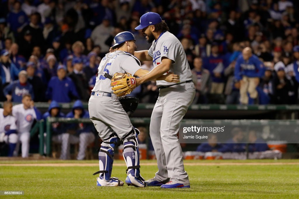 Austin Barnes #15 and Kenley Jansen #74 of the Los Angeles Dodgers celebrate after beating the Chicago Cubs 11-1 in game five of the National League Championship Series at Wrigley Field on October 19, 2017 in Chicago, Illinois. The Dodgers advance to the 2017 World Series.