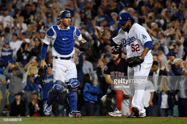 Austin Barnes and Pedro Baez of the Los Angeles Dodgers celebrate the out during the tenth inning against the Boston Red Sox in Game Three of the...