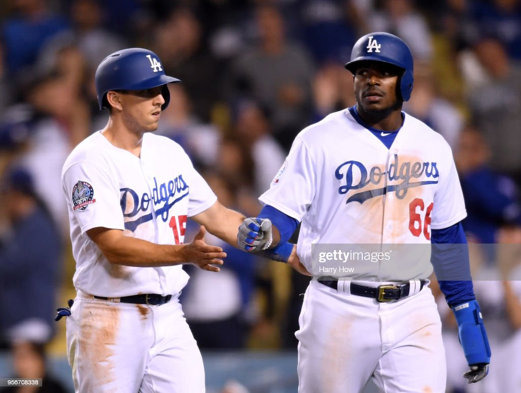 Austin Barnes #15 and Yasiel Puig #66 celebrate their runs from a Chase Utley #26 double to take a 6-3 lead during the eighth inning against the Arizona Diamondbacks at Dodger Stadium on May 9, 2018 in Los Angeles, California.