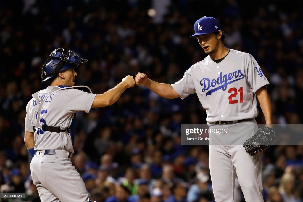 Austin Barnes #15 and Yu Darvish #21 of the Los Angeles Dodgers celebrate before Darvish is relieved in the seventh inning against the Chicago Cubs during game three of the National League Championship Series at Wrigley Field on October 17, 2017 in Chicago, Illinois.
