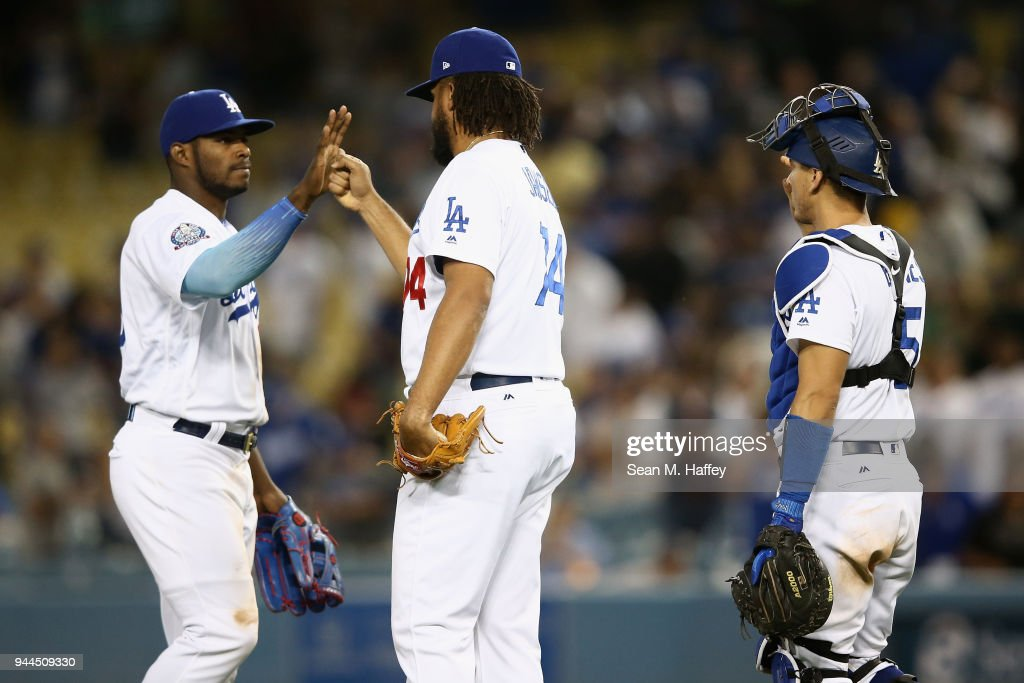 Austin Barnes #15, Kenley Jansen #74 and Yasiel Puig #66 of the Los Angeles Dodgers celebrate after defeating the Oakland Athletics 4-0 in a game at Dodger Stadium on April 10, 2018 in Los Angeles, California.