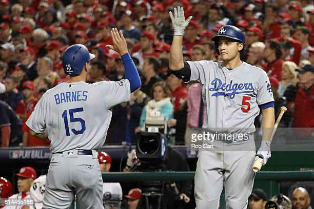 Austin Barnes of the Los Angeles Dodgers celebrates with teammate Corey Seager after scoring off of an RBI single hit by Carlos Ruiz in the seventh...