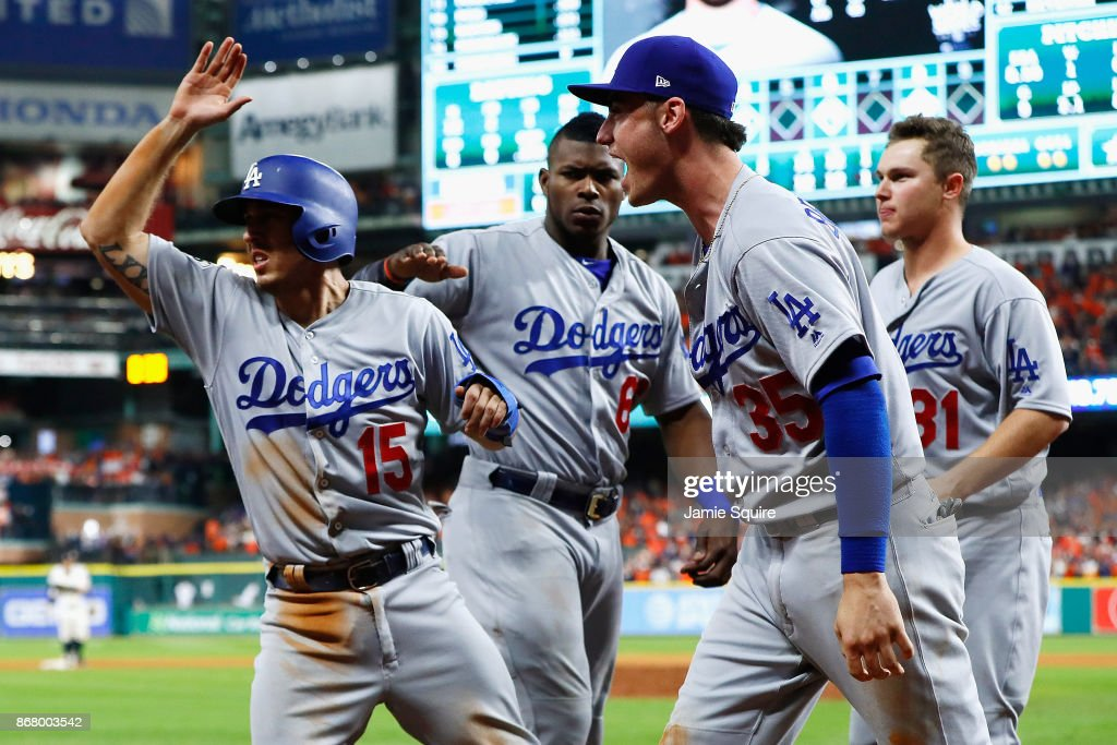Austin Barnes #15 of the Los Angeles Dodgers celebrates with Yasiel Puig #66, Cody Bellinger #35 and Joc Pederson #31 after scoring on a single during the ninth inning against the Houston Astros in game five of the 2017 World Series at Minute Maid Park on October 29, 2017 in Houston, Texas.