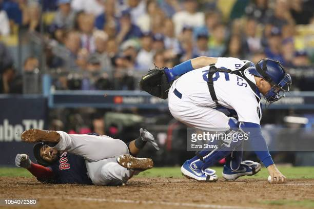 Austin Barnes of the Los Angeles Dodgers collides with Eduardo Nunez of the Boston Red Sox while fielding a wild pitch during the thirteenth inning...