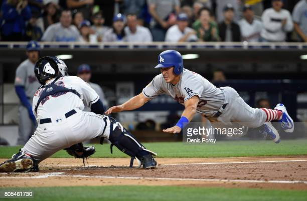 Austin Barnes of the Los Angeles Dodgers dives to home plate before being tagged out by Austin Hedges of the San Diego Padres during the fourth...