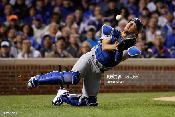 Austin Barnes of the Los Angeles Dodgers fails to catch a foul ball in the fifth inning against the Chicago Cubs during game three of the National...