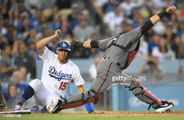 Austin Barnes of the Los Angeles Dodgers gets past Alex Avila of the Arizona Diamondbacks to score in the third inning at Dodger Stadium on March 30...