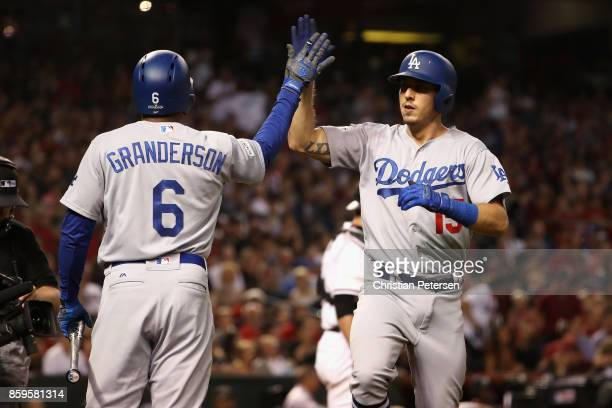 Austin Barnes of the Los Angeles Dodgers high fives team mate Curtis Granderson after hitting a one run home run during the sixth inning of the...