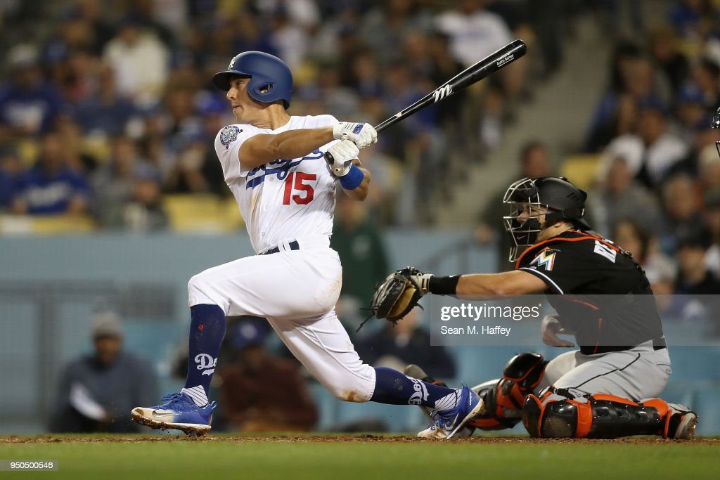 Austin Barnes #15 of the Los Angeles Dodgers hits a double as J.T. Realmuto #11 of the Miami Marlins looks on during the fifth inning of a game at Dodger Stadium on April 23, 2018 in Los Angeles, California.