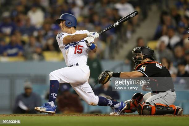Austin Barnes of the Los Angeles Dodgers hits a double as JT Realmuto of the Miami Marlins looks on during the fifth inning of a game at Dodger...
