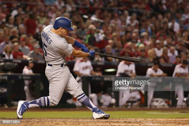 Austin Barnes of the Los Angeles Dodgers hits a one run home run during the sixth inning of the National League Divisional Series game three against...