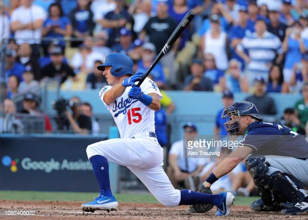 Austin Barnes of the Los Angeles Dodgers hits a RBI single in the fifth inning of Game 5 of the NLCS against the Milwaukee Brewers at Dodger Stadium...