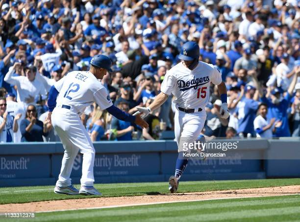 Austin Barnes of the Los Angeles Dodgers is congratulated by third base coach Dino Ebel of the Los Angeles Dodgers after hitting a one run home run...