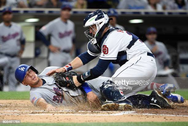 Austin Barnes of the Los Angeles Dodgers is tagged out at the plate by Austin Hedges of the San Diego Padres during the fourth inning of a baseball...
