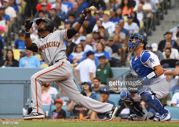 Austin Barnes of the Los Angeles Dodgers looks on as Alen Hanson of the San Francisco Giants hits a sacrifice fly to score Mac Williamson of the San...