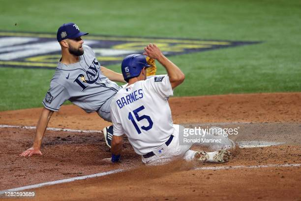 Austin Barnes of the Los Angeles Dodgers slides in safely past Nick Anderson of the Tampa Bay Rays to score a run on a wild pitch during the sixth...
