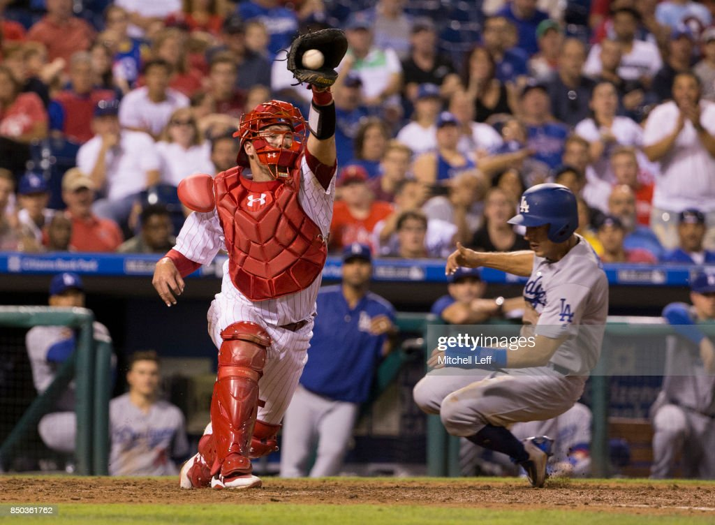 Austin Barnes #15 of the Los Angeles Dodgers slides past Andrew Knapp #34 of the Philadelphia Phillies to score a run in the top of the eighth inning at Citizens Bank Park on September 20, 2017 in Philadelphia, Pennsylvania. The Phillies defeated the Dodgers 7-5.