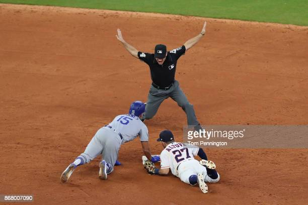 Austin Barnes of the Los Angeles Dodgers slides safely in to second base with a double as Jose Altuve of the Houston Astros attempts the tag during...