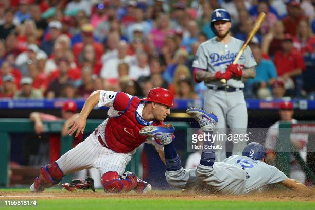 Austin Barnes of the Los Angeles Dodgers steals home before the tag of catcher J.T. Realmuto of the Philadelphia Phillies during the fourth inning of...