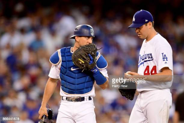 Austin Barnes talks with Rich Hill of the Los Angeles Dodgers during the third inning of game two of the 2017 World Series at Dodger Stadium on...