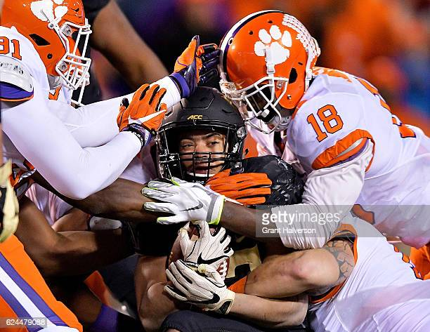 Austin Bryant and Jadar Johnson of the Clemson Tigers tackle Cade Carney of the Wake Forest Demon Deacons during the game at BBT Field on November 19...